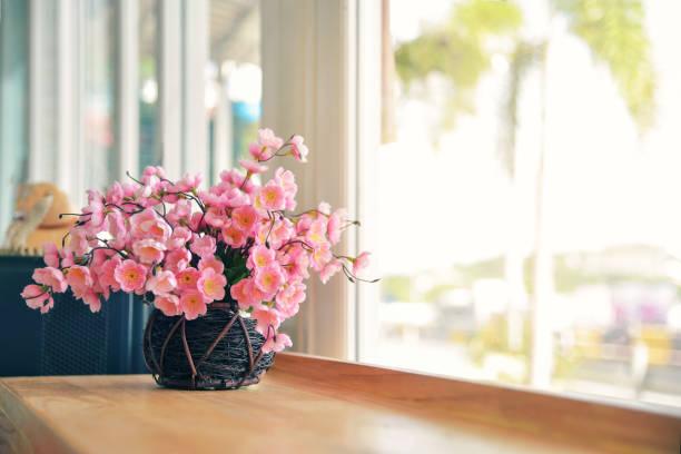 Floare frumoasă în vas ceramic pusă pe pervaz în lumina soarelui
