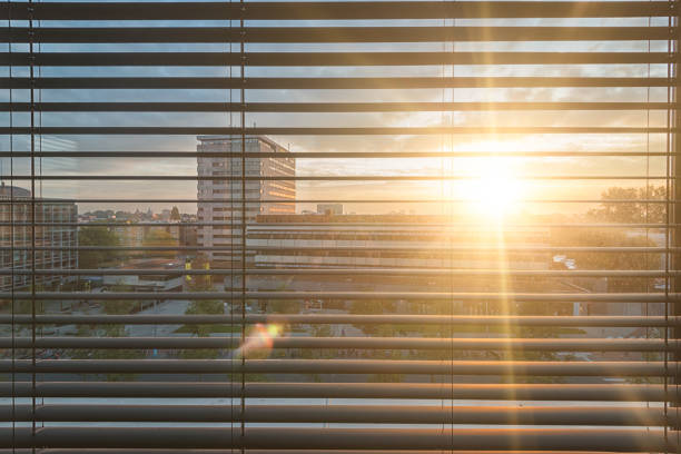 The blinds in a hotel room in amsterdam have turned down. The slats are tilted. The morning sun shines through them. It's blinding. The sun's rays penetrate the room. Beautiful morning atmosphere in an unknown city.