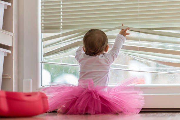 Cute little baby girl wearing a pink tutu lifting the blinds on the window so she can peer outside at the garden in a low angle rear view.