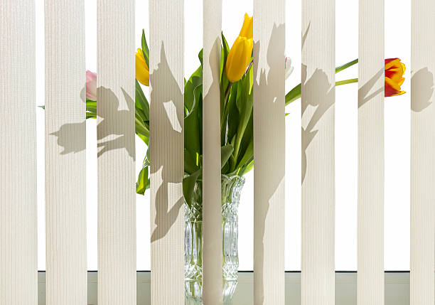 Bouquet of flowers in a vase standing on the windowsill for vertical blinds