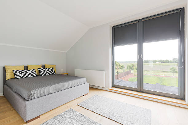 Contemporary bedroom in a detached house outside the city, with a large balcony window overlooking the backyard and fields