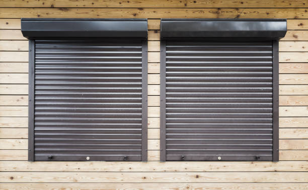 Wooden wall with two windows protected with roller shutters, background texture